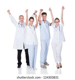 Diverse medical team of male and female doctors and nurses celebrating a successful outcome to a case