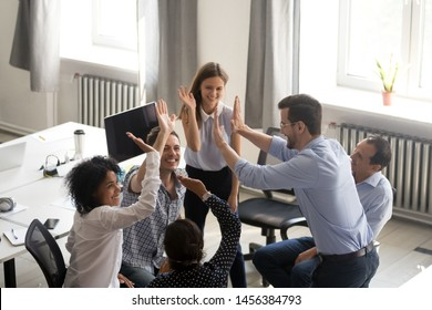 Diverse millennial colleagues give high five engaged in informal teambuilding activity in office, multiracial young coworkers involved in creative group meeting, have motivational briefing or talk