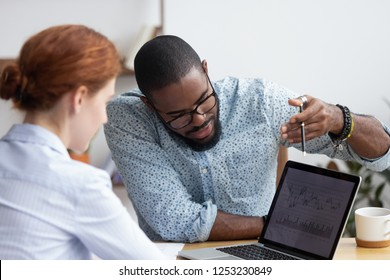 Diverse millennial colleagues working together analyzing diagram looking at computer screen. Black mentor helps female apprentice understand corporate program explaining interface showing on monitor