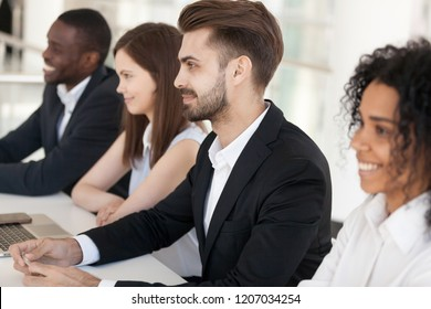 Diverse millennial employee sit in row at table looking at presenter or job candidate smiling, multiethnic workers like speaker or applicant, impressed recruiters feel positive at interview