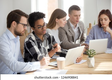 Diverse millennial employees cooperate working at laptops in office together, multiethnic workers use computers involved in training or teambuilding activity, teams brainstorm at business meeting