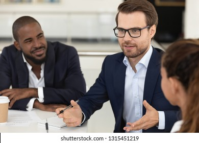 Diverse millennial employees sitting at desk gathered together at boardroom, focus on caucasian team leader, mentor or business coach talking at meeting with interns, communication cooperation concept