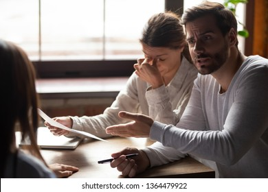 Diverse millennial people sitting at table in office indignant man accusing incompetent unqualified woman colleague pointing on financial report with mistakes, lack of education and knowledge concept