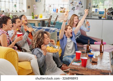 Diverse mix of friends sports fans watching winning football match on TV at home Celebrating winning goal huddled on couch shouting excited  sharing snacks drinking beer