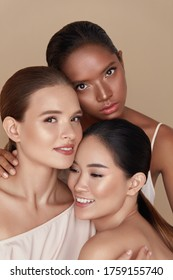 Diverse. Models Beauty Portrait. Ethnic Women With Nude Makeup And Glowing Skin Standing Together Against Beige Background. Caucasian, Asian And Mixed Race Female Hugging And Looking At Camera.