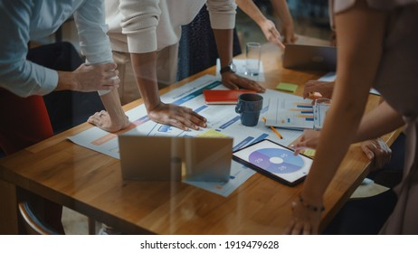 Diverse Multi Ethnic Team of Professional Businesspeople Meeting in the Modern Office Conference Room. Creative Team Gathers Around Table to Discuss App Design, Analyze Data. Focus on Desk and Hands