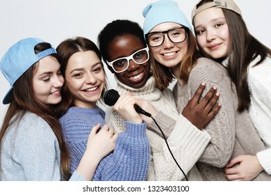 diverse multi nation girls group, teenage friends company cheerful having fun with microphone