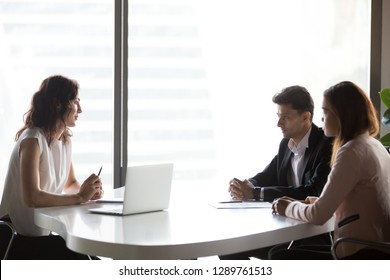 Diverse multi-ethnic business people communicating sitting at office meeting table, serious multiracial hr talking to applicant at job interview, recruitment, consulting and negotiations concept