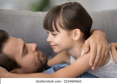 Diverse multi-ethnic family indoors. Close up little daughter embracing loving father lying together on sofa at home. Love tenderness understanding and warm relationship between parent and kid concept