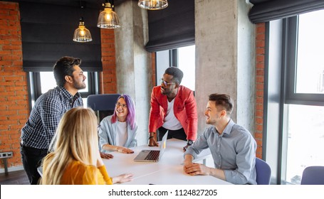 Diverse multiethnic group of young businesspeople in office boardroom gathering together around white table, discussing their business strategy and sharing information