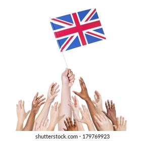 Diverse Multiethnic Hands Holding and Reaching For The Flag of Great Britain