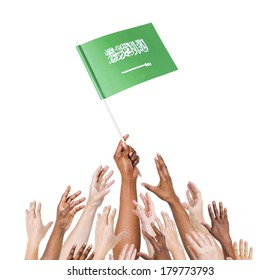 Diverse Multiethnic Hands Holding and Reaching For The Flag of Saudi Arabia