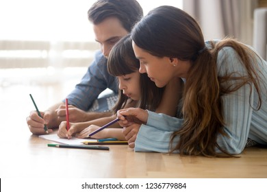 Diverse multiracial family married couple with little adorable daughter lying on wooden warm floor at modern home drawing together on paper using colored pencils. Child development and hobby concept