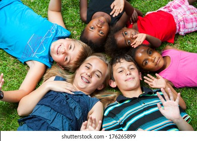 Diverse multiracial group of kids laying together joining heads.