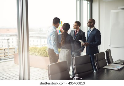 Diverse multiracial management team standing grouped in front of a large bright window in the conference room discussing colorful memos on the glass