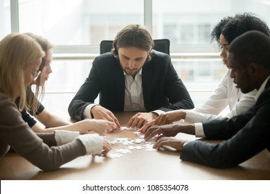 Diverse office executive team assembling puzzle finding good business solutions together, multiracial businesspeople engaging in successful teamwork expressing corporate unity, teambuilding concept