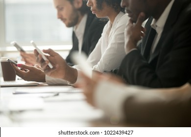 Diverse office people working on mobile phones, corporate employees holding smartphones at meeting, serious multiracial businessmen and businesswomen using gadgets online apps for business, close up