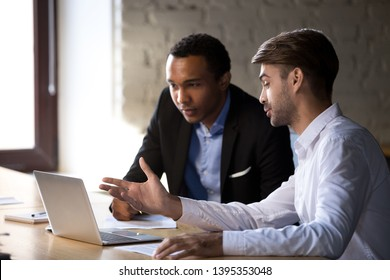 Diverse office workers businessmen entrepreneurs brainstorm discuss analyse online project looking at laptop screen, mentor teach intern. Support assistance common aim in business and teamwork concept
