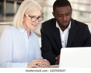 Diverse office workers busy working at laptop during business negotiations, black millennial employee teach middle-aged colleague using computer, young mentor or coach training mature coworker