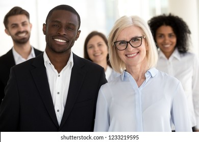 Diverse old and young professional business coaches or corporate leaders with team people portrait, smiling multiracial executive partners, african caucasian company staff group looking at camera