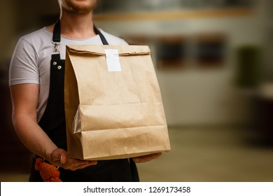 Photo of Diverse of paper containers for takeaway food. Delivery man is carrying