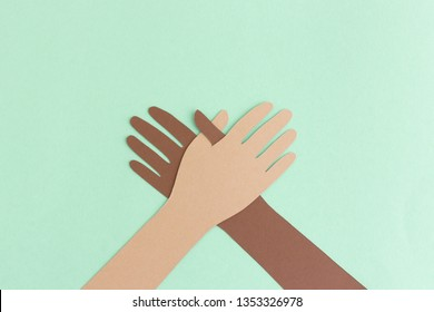 Diverse paper cutout of hands in stack on blue background