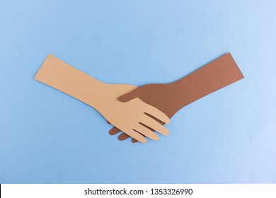 Diverse paper hands shaking in agreement on blue background