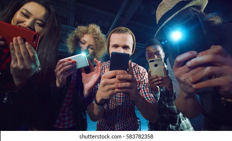 Diverse people bending to camera and taking shots on their smartphones.