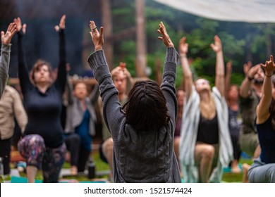 Diverse people enjoy spiritual gathering A large group of multigenerational people are seen in a peaceful yoga pose with arms raised in air during a woodland retreat for body and mind.
