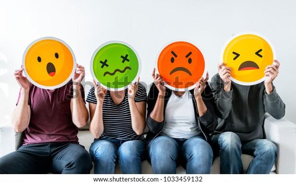Diverses personnes tenant un émoticône
