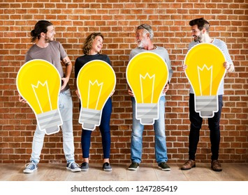 Diverse people holding light bulb icons