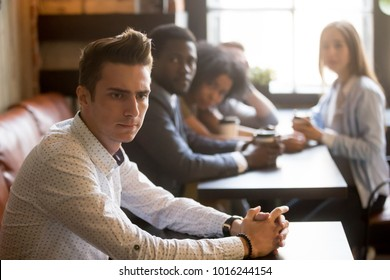 Diverse people looking at thoughtful frustrated man in cafe, sad misunderstood guy feels offended ignoring multiracial friends sitting alone at table, excluded outstand person suffers from bullying