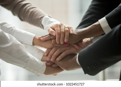 Diverse people putting stacked hands together promising help and support starting common business, black and white multiracial group unite at motivating training, team building concept, close up view
