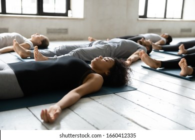 Diverse people resting after work out lying on carpets performing Shavasana or Corpse Dead position focus on African female, final pose of yoga class deep restoration, body and mind relaxation concept