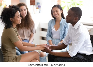 Diverse people sit in circle on chairs do exercise express gratitude improve work collective relations team building concept. African couple hold hands show appreciation at psychological rehab session