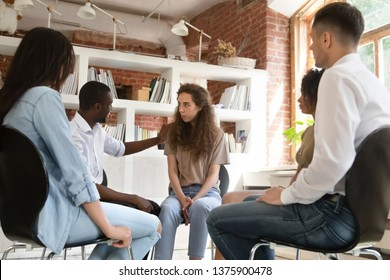 Diverse people sit in circle together at group therapy discuss share personal problems, african psychologist supporting encouraging newcomer shy girl. Medical detox center, psychological help concept