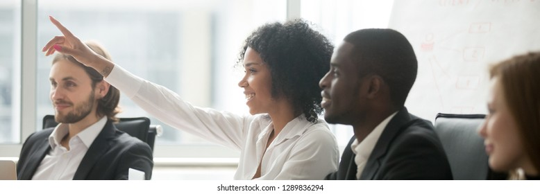 Diverse people sitting at boardroom, african woman raise hand ask question during seminar conference, corporate education or volunteer voting concept. Horizontal photo banner for website header design
