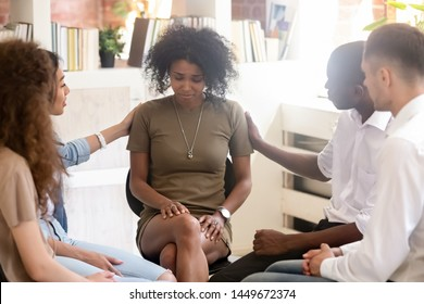 Diverse people supporting unhappy African American woman at therapy session, touching shoulders, sitting in circle, psychological help, trust and support, drug alcohol addiction treatment