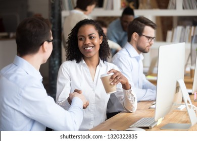 Diverse people working in modern office room, focus on black african female greeting caucasian male sitting together in coworking space shaking hands. Two multinational business people meeting concept