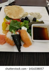 A diverse plate of food with pita bread, houmous, dips, olives, salad, sushi and dolmades