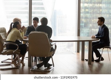 Diverse recruiters discuss male applicant candidature for job vacancy during interview in modern office, worried man candidate wait for employer decision at hiring. Employment, recruitment concept