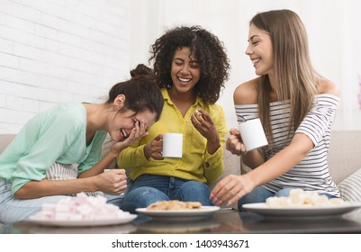Diverse roommates drinking coffee, eating cookies and laughing at home