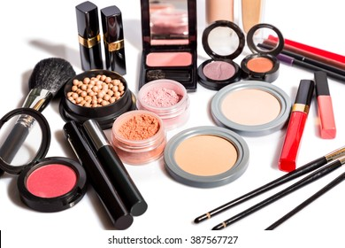 Diverse selection of brushes along side makeup powders, eye shadow, red and pink lipsticks and compact with foundation