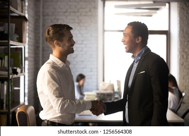 Diverse smiling businessmen shake hands getting acquainted introducing make first impression, happy friendly african and caucasian workers handshaking talking greeting, welcoming new employee concept