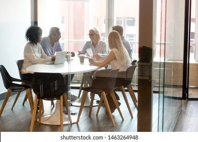 Diverse smiling businesspeople sit in boardroom having active conversation discussing business projects at meeting, multiethnic colleagues brainstorm talking sharing thoughts negotiate at briefing
