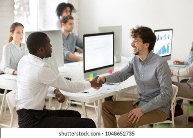 Diverse smiling colleagues shake hands in office, happy caucasian manager handshaking satisfied african client customer making deal agreement, thanking for help advice or successful teamwork concept