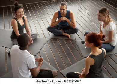 Diverse smiling people sitting on mats in circle relaxing talking before yoga training, happy multiracial friends group discuss healthy lifestyle motivation after pilates fitness class in gym studio