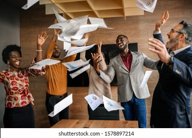 Diverse South African business team throwing papers in the air. Team celebrating a successful financial end of year