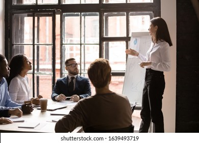 Diverse staff listen woman business trainer at corporate training in boardroom. Clients and firm representative take part in group meeting, presentation information new knowledge for audience concept