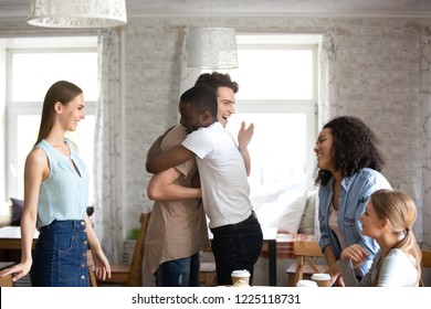 Diverse students gathered together during lunch. Guys buddies best friends hugging greeting each other at meeting in cafe surrounded by attractive multi-ethnic girls. Friendship and reunion concept